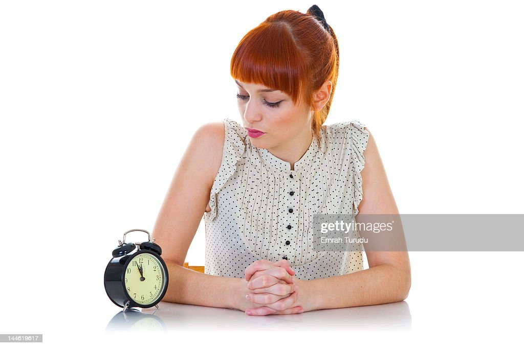 Young woman sitting with alarm clock