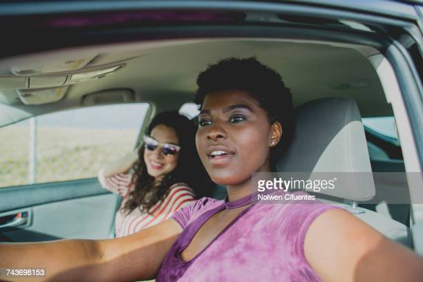 Young woman sitting with female friend looking away while sitting in car on sunny day