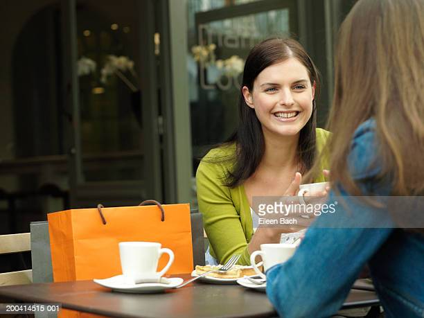 Young woman sitting with friend at outdoor cafe having drinks, smiling