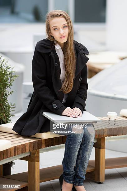Young woman sitting with laptop and coffee.