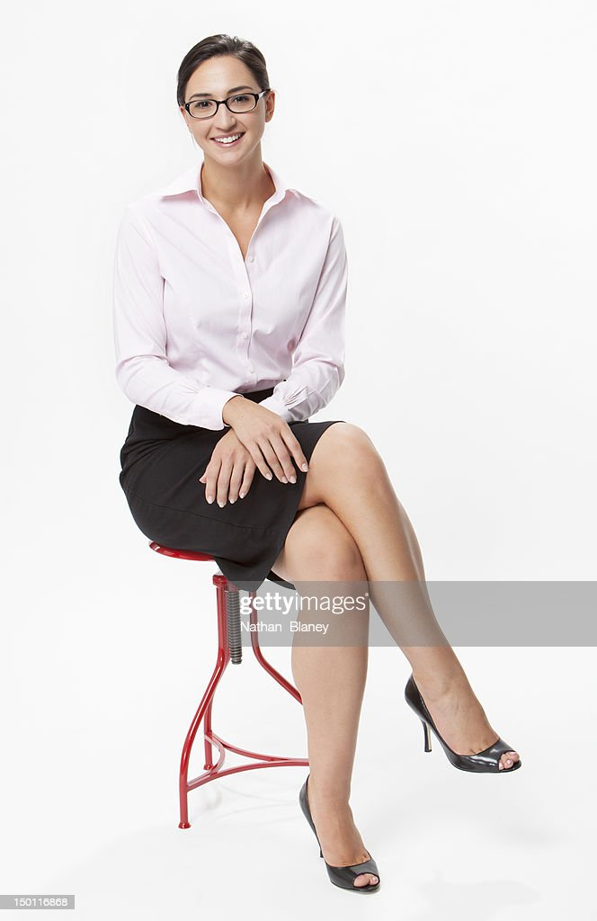 Young woman sitting with legs crossed : Stock Photo
