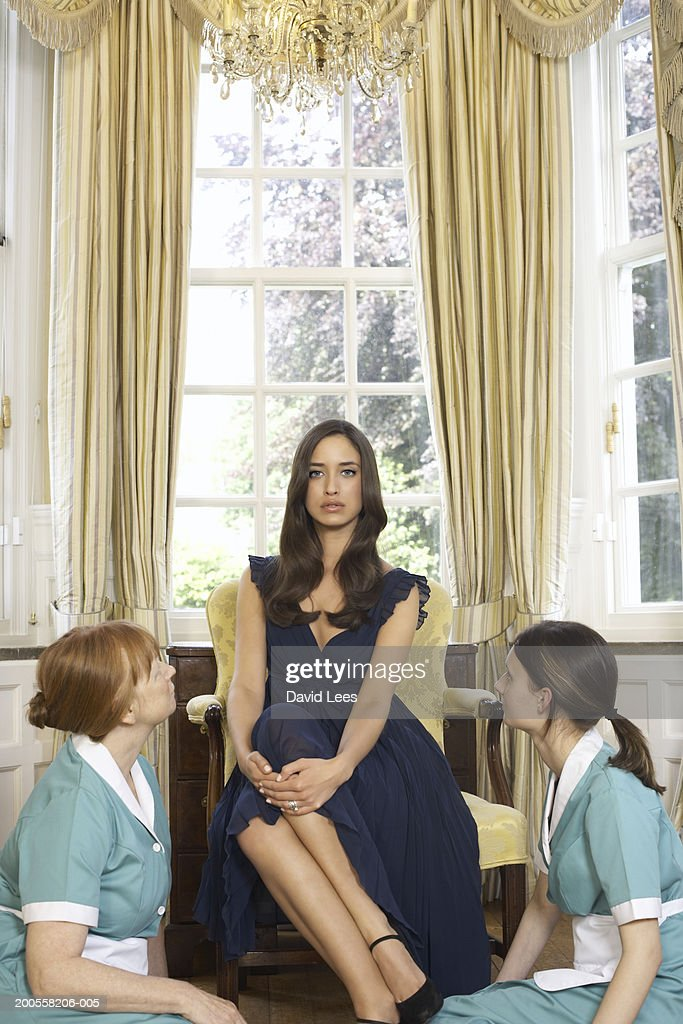 Young woman sitting with maids : Stock Photo