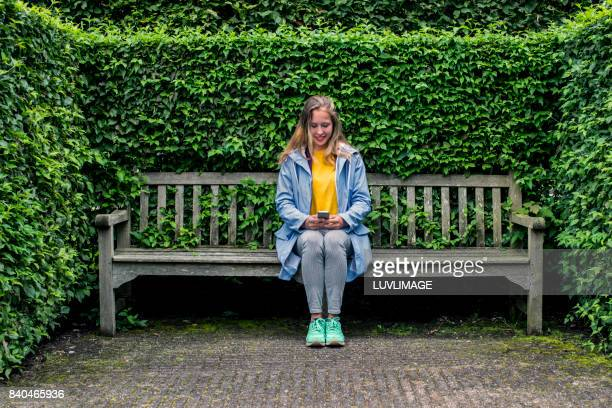 Young woman sitting with mobile phone.