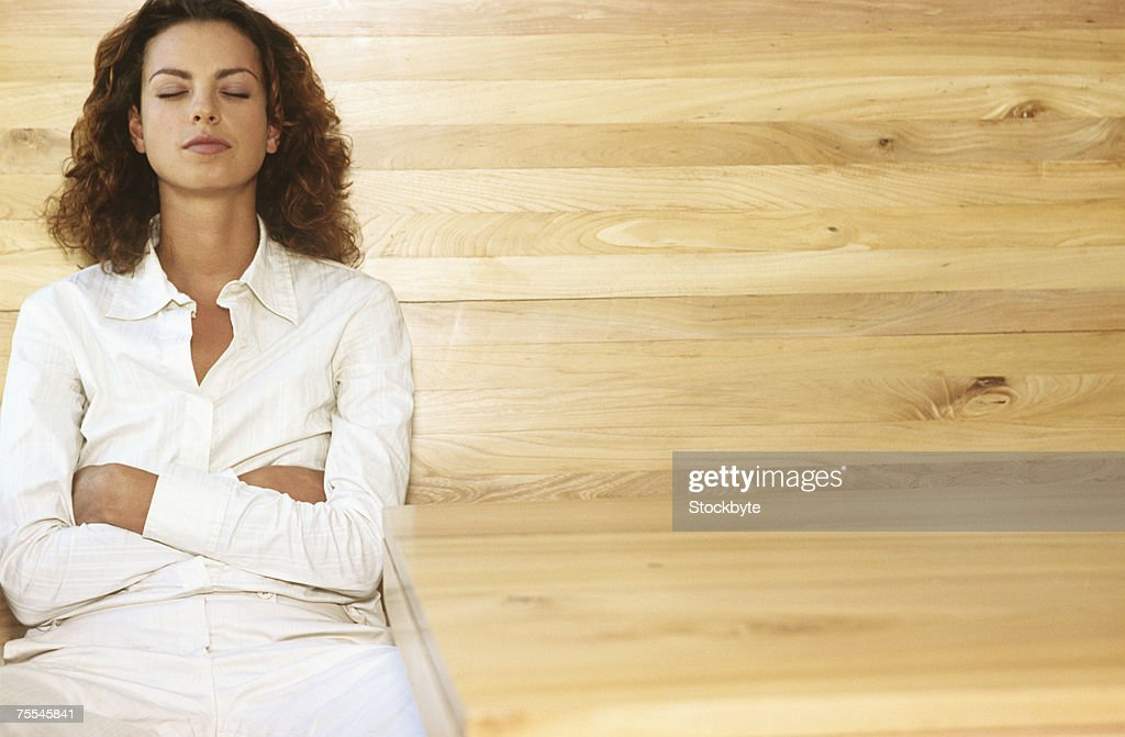 Young woman sitting,with closed eyes and arms crossed : Stockfoto