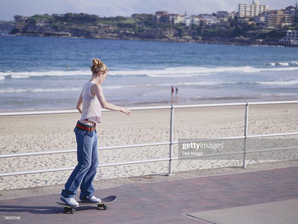 Young woman skateboarding on pathway, near beach : Stock Photo