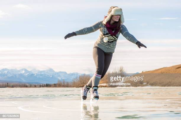 Young woman skates across frozen lake, mtns behind