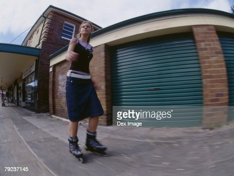 Young woman skating on pavement : Stock Photo
