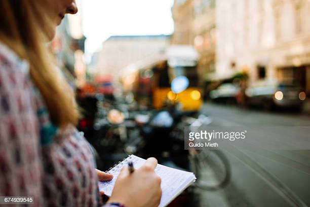 Young woman sketching in the city.