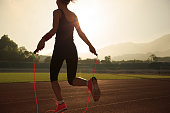 Young woman skipping rope during sunny morning on stadium track