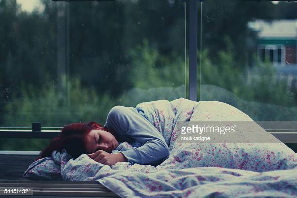 Young woman sleeping at bus shelter