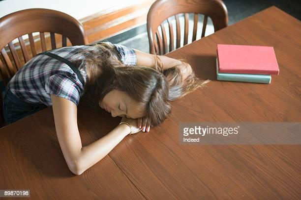 Young woman sleeping at table, high angle view