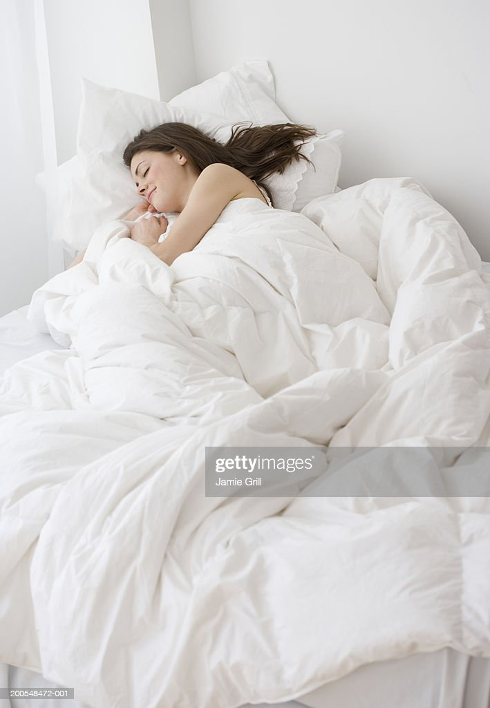 Young woman sleeping in bed, elevated view : Stock Photo