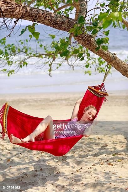 Young woman sleeping in hammock on beach