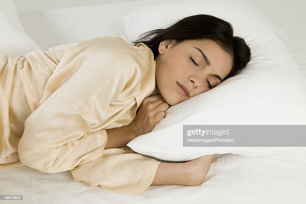 Young woman sleeping on a bed : Stock Photo