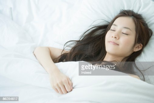 Young woman sleeping on bed, portrait : Stock Photo