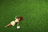 Young woman sleeping on grass with book in hand, view from above
