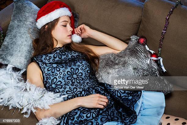 Young woman sleeping on sofa wearing christmas hat