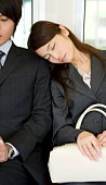 Young woman sleeping on the seat, resting head on man's shoulder
