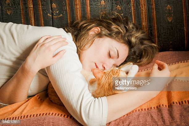 Young woman sleeping together with ginger cat