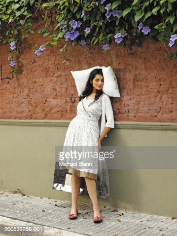 Young woman sleeping with pillow against wall