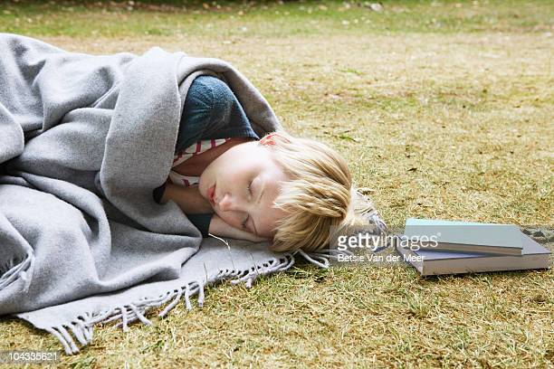 young woman sleeping, wrapped in blanket in park.