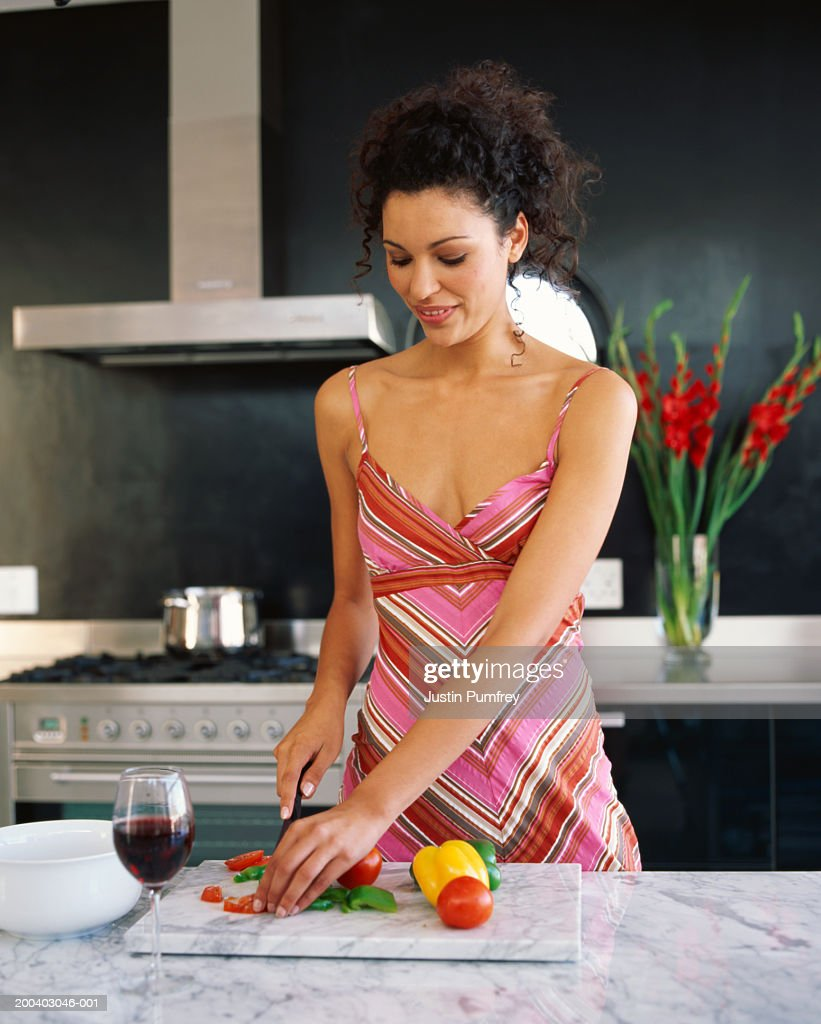 Young woman slicing tomatoes and peppers in kitchen, smiling : Stock Photo