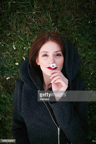 Giovane donna odorare daisy in erba