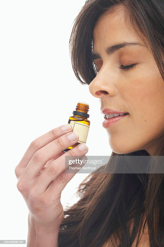 Young woman smelling aromatherapy oil, eyes closed