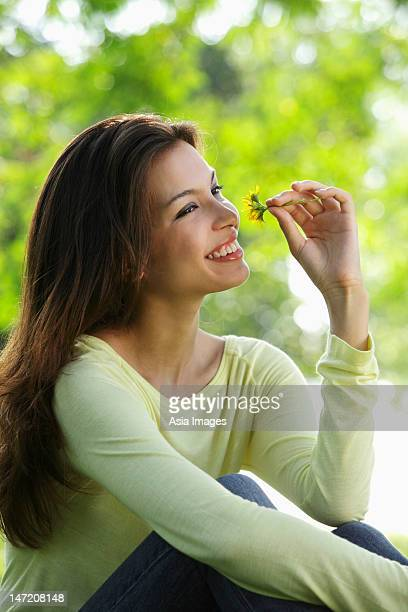 young woman smelling flower and smiling