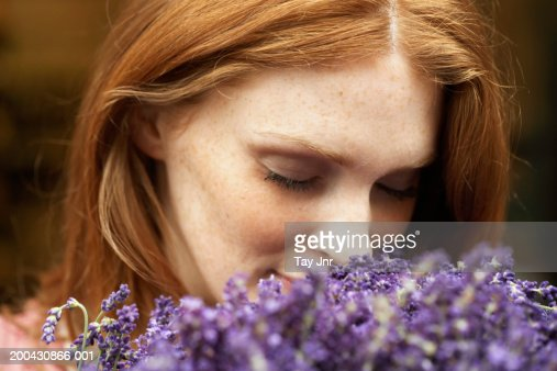 Young woman smelling lavendar, eyes closed, close-up : Stock Photo