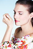 Young woman smelling perfume on her wrist