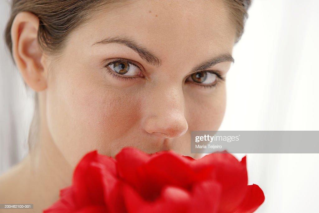 Young woman smelling petals, close-up, portrait : Stock Photo