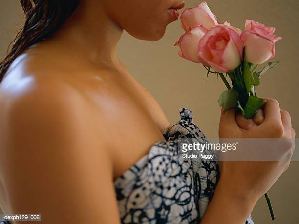 Young woman smelling rose, close-up