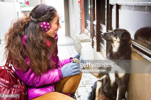 Young woman smiles and holds stray dog paw