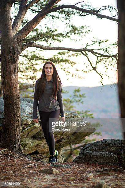 A young woman smiles at the camera while hiking.