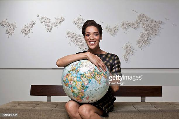 Young woman smiling and holding a globe in her lap