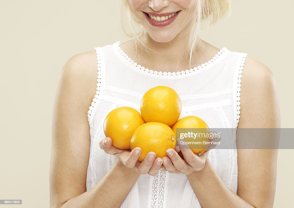 young woman smiling and holding oranges