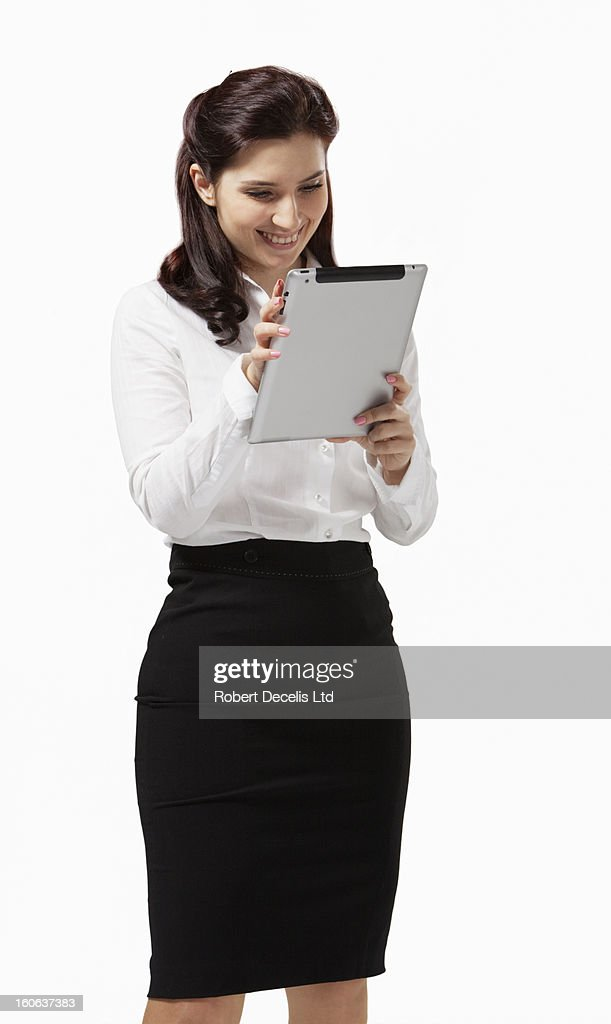 Young woman smiling and reading tablet : Stock Photo