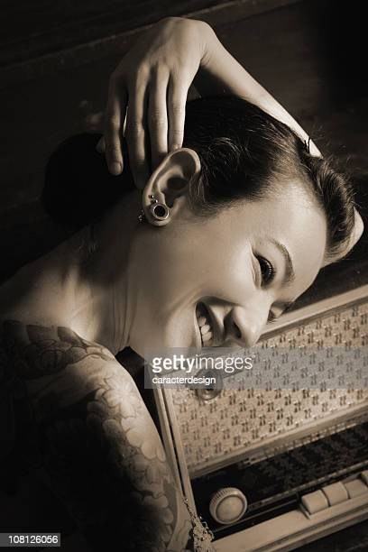 Young Woman Smiling and Resting Head on Antique Radio