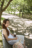 Young woman smiling and sitting on bench, holding iced coffee