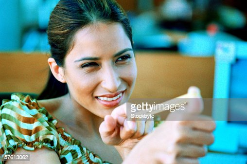 Young woman smiling and stretching a rubber band between her fingers