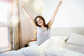 young woman smiling and stretching in bed