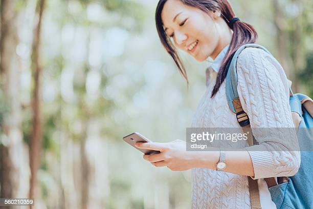 Young woman smiling and text messaging in nature