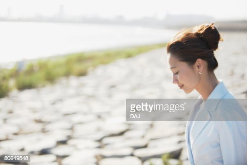 Young woman smiling at seaside, differential focus : Foto de stock
