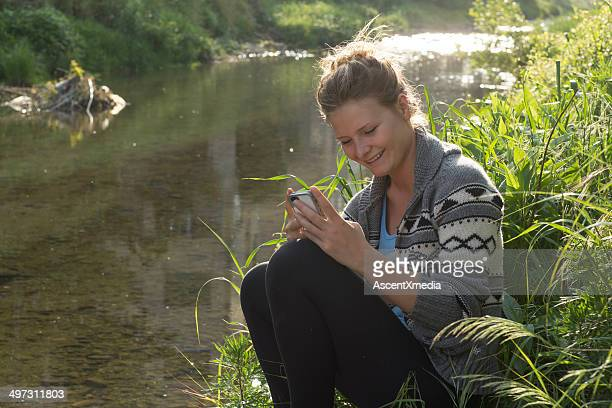 Young woman smiling at smart phone text