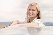 Young woman smiling beside car