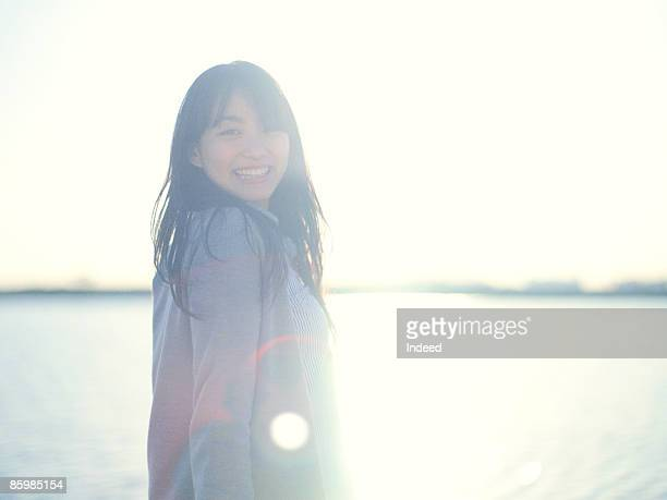Young woman smiling by the river, portrait