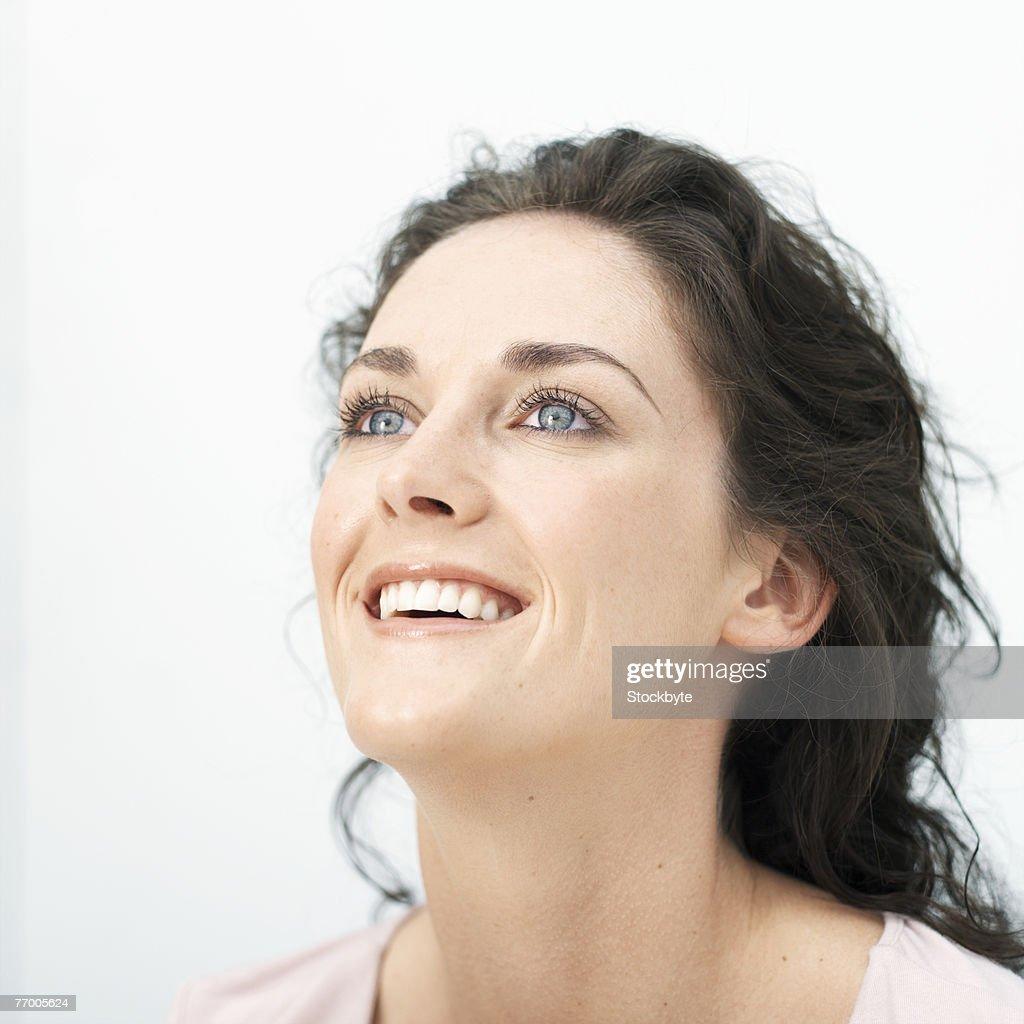 Young woman smiling, close-up, studio shot : Stock Photo