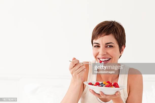 Junge Frau lächelnd Essen Obstschale