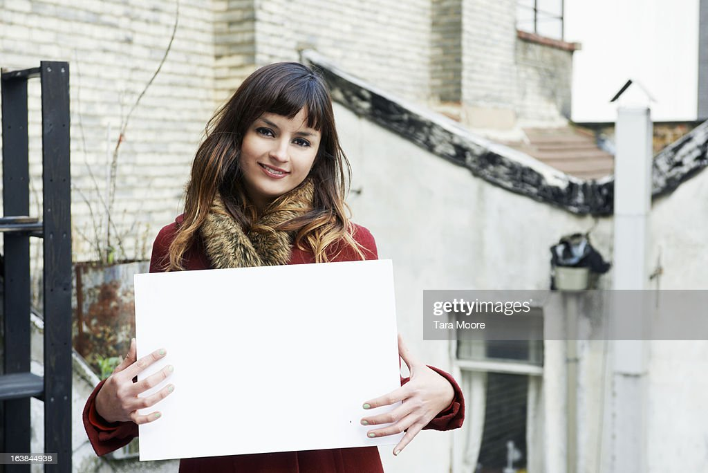 young woman smiling holding blank sign : Stock-Foto